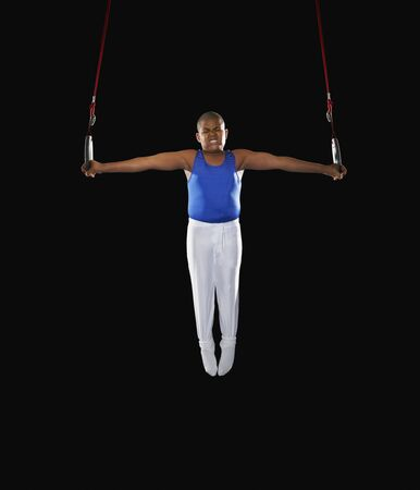 jeopardizing: Young boy balancing on the gymnastic rings