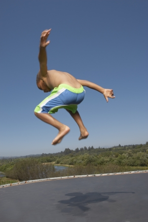 togs: Young boy jumping on a trampoline