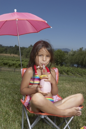 Young girl drinking juice in a lawn chair Standard-Bild