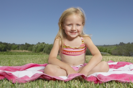 'young things': Young girl relaxing on a towel outdoors LANG_EVOIMAGES