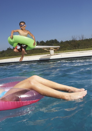togs: Children playing with inner tubes in a pool