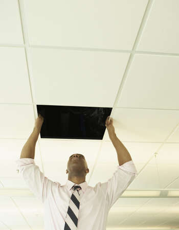 ceiling: Businessman replacing a ceiling tile LANG_EVOIMAGES