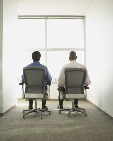 swivel: Businessmen sitting in swivel chairs in empty office space