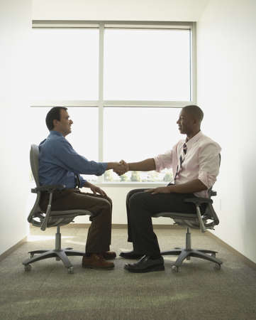swivel chairs: Businessmen shaking hands in swivel chairs