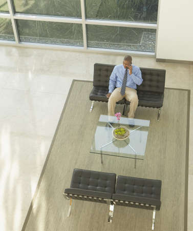 Businessman talking on a cell phone in lobby area Stock Photo - 16089302