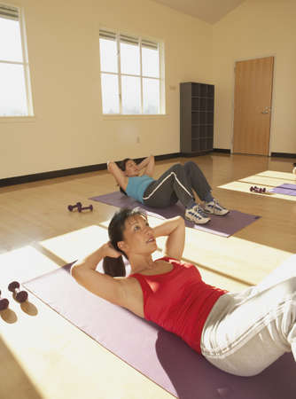 Young women doing crunches Stock Photo - 16089314