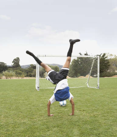 Young girl doing a cartwheel on soccer pitch Stock Photo - 16089317