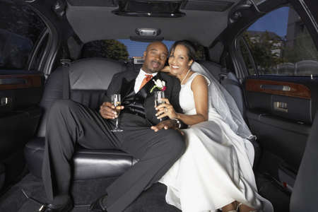 honeymooner: Newlyweds drinking champagne in their limo