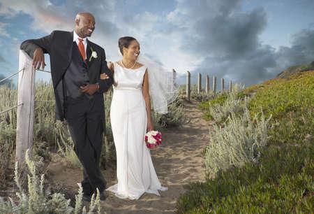 honeymooner: Newlyweds walking on the beach