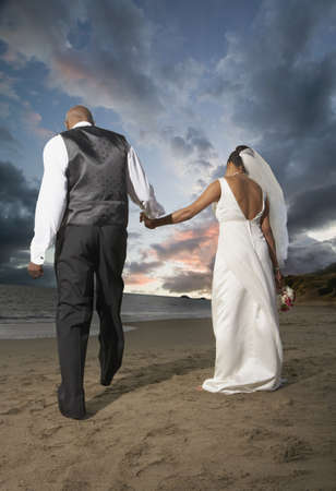 Newlyweds walking on the beach Stock Photo - 16089335