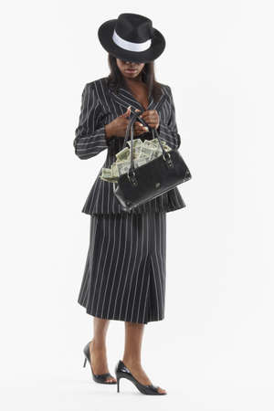 Businesswoman holding a purse full of money Stock Photo - 16089345