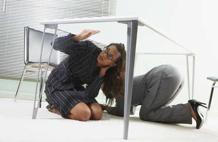 obscuring: Businesswomen crouching beneath a desk
