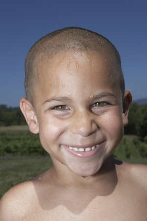young boy smiling: Young boy smiling for the camera with wet hair LANG_EVOIMAGES