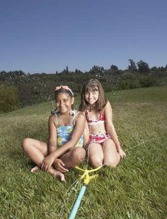 lawn sprinkler: Young girls smiling for the camera LANG_EVOIMAGES