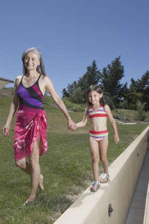 gramma: Senior woman and granddaughter walking together LANG_EVOIMAGES