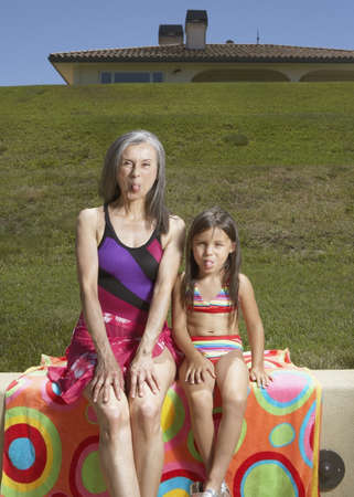 fond of children: Senior woman and her granddaughter sticking their tongues out