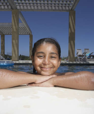 saturating: Young girl smiling for the camera in a swimming pool