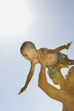 togs: Father carrying his son in the air