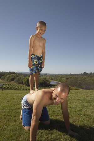 poppa: Young boy standing on his fatherÃŒs back