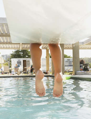 only 1 girl: Feet dangling off the end of a diving board