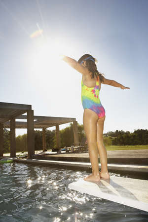 kids swimming pool: Little girl standing on the end of a diving board