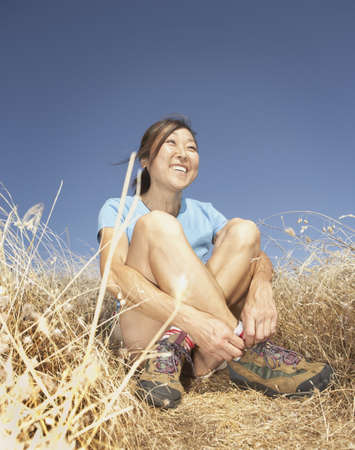relishing: Middle-aged woman smiling in tall grass