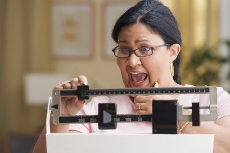 Shocked woman weighing herself 스톡 콘텐츠