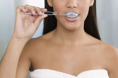 lower section view: Young woman brushing her teeth