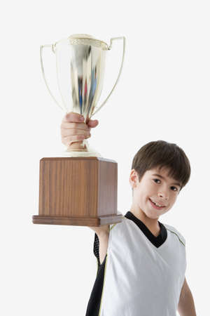 prevailing: Young athlete holding up trophy triumphantly LANG_EVOIMAGES