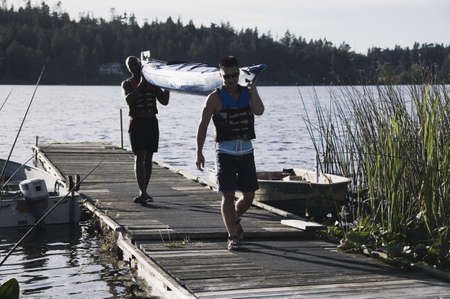 Young men carrying canoe away from lake LANG_EVOIMAGES