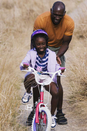 milestones: Young man pushing his daughter on her bike