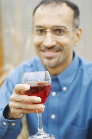 Man holding out his wine in toast Stock Photo - 16089512