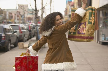 stepping: Young woman holding up shopping bags