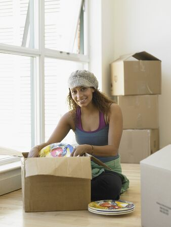 cardboard only: Young woman unpacking dishes