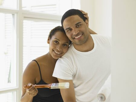 Couple posing for the camera as they paint their house
