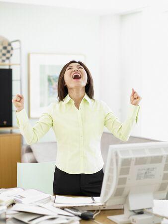front desk: Businesswoman celebrating at her desk