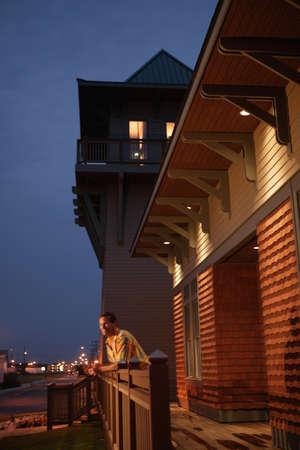 nite: Man leaning over wooden banister LANG_EVOIMAGES
