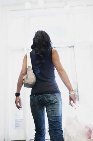 go inside: Young woman carrying shopping bags
