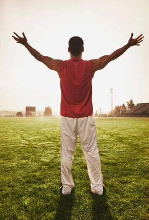 idealism: Male athlete holding his arms out on football field