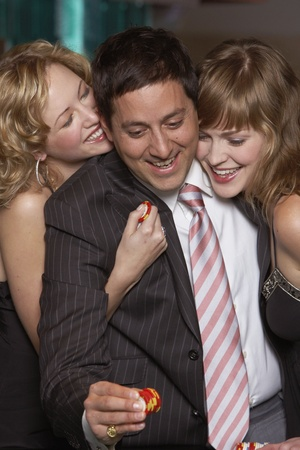 Man gambling as women fawn over him Stock Photo - 16089623