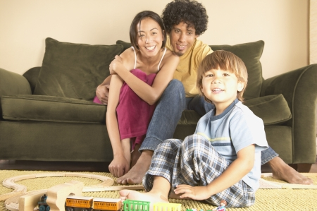 davenport: Mother and father sitting on a couch with their son playing with toys on the floor