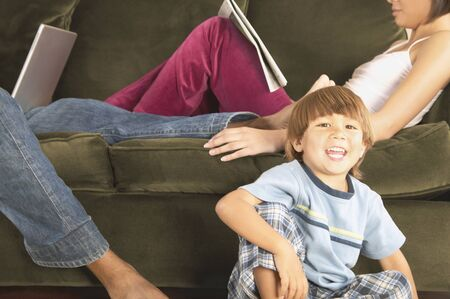 Portrait of a child sitting on the floor smiling with his parents sitting on a couch behind him Stock Photo - 16089628