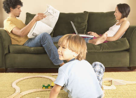 americal: Mother and father sitting on a couch with a boy playing on the ground