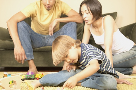 americal: Boy playing with toys on the ground with his parents sitting behind him