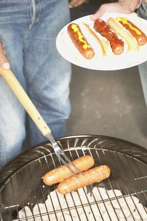 chargrill: Person cooking sausages on a barbeque grill