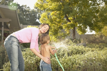Mother and son watering the garden with a garden hose LANG_EVOIMAGES