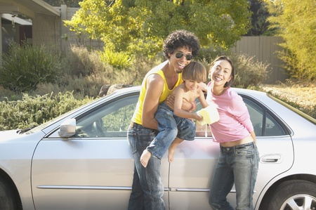 car wash: Family standing in front of a car in a driveway