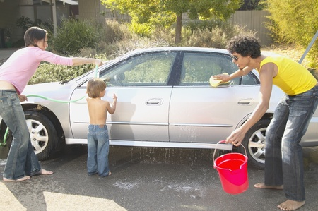 Family washing a car in a driveway LANG_EVOIMAGES