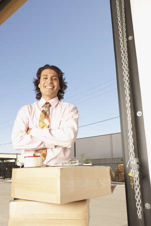 1 person: Businessman standing by cardboard boxes in a garage LANG_EVOIMAGES