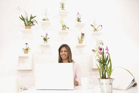 花の壁が机の後ろに若い女性
